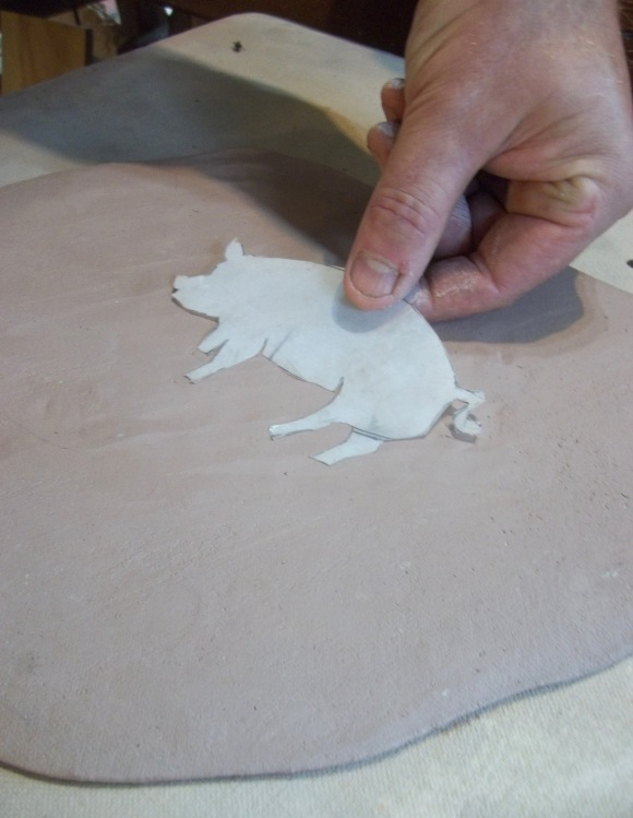Jon places a thin plastic shape of a pig to act as a stencil on stoneware clay.